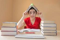 Ung flickastudent med högen av böcker och anmärkningar som inomhus studerar Royaltyfri Fotografi