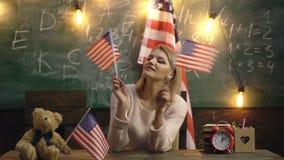 Ung flickastudent på bakgrunden med amerikanska flaggan Begrepp f?r l?ra f?r engelskt spr?k Engelska som studerar, talar stock video