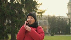 Ung flickastudenten talar på telefonen parkerar in nära universitet stock video