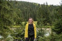 Ung flickaturist på bakgrunden av den berg-, barrskog- och bergfloden under en tur till Carpathiansna royaltyfria bilder