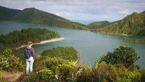 Ung flickaturisten står nära en bergsjö på en höjd som förbiser havet arkivfilmer