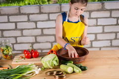Ung flickatvagninggrönsaker, som hon buteljerar dem Arkivbild