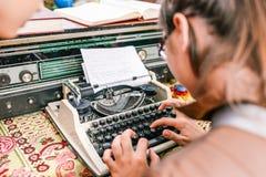 Ung flickatyper på en skrivmaskin Journalisten skrivar ut nyheterna Affärsidé eller nyheterna royaltyfri bild