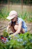 Ung flickaväxtplanta av en blomma royaltyfri bild