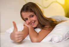 Ung flickavisningen tummar upp tecknet med en grina, grunt djup Royaltyfria Foton