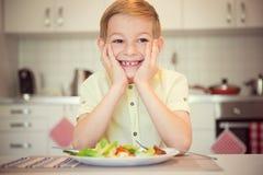 Ung flitig lycklig pojke på en tabell som äter sunt mål royaltyfria foton