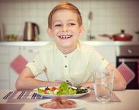 Ung flitig lycklig pojke på en tabell som äter sunt mål med cu royaltyfria foton