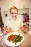 Ung flitig lycklig pojke på en tabell som äter sunt mål med cu arkivfoton