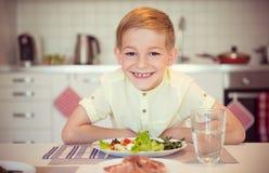 Ung flitig lycklig pojke på en tabell som äter sunt mål med cu royaltyfria bilder