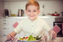 Ung flitig pojke på en tabell som äter sunt mål med bestick royaltyfri foto