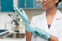 Ung forskare i glasögon som bär skyddande handskar i labb royaltyfria foton