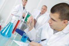 Ung forskare som blandar kemisk flytande för experiment Arkivfoton
