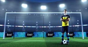 Ung fotbollspelare med bollen som är främst av målet på en professi arkivfoto