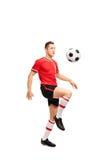 Ung fotbollsspelare som jonglerar en boll Royaltyfri Foto