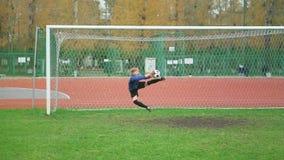 Ung fotbollsspelare som sparkar bollen på stadion stock video