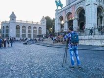 Ung fotograf med tripoden som är främst av den Sacre Coeur basilikan på Montmartre i Paris, Frankrike Royaltyfri Foto