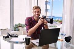 Ung fotograf som arbetar från hans hem- studio royaltyfria foton