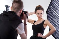 Ung fotograf som arbetar med den yrkesmässiga modellen Fotografering för Bildbyråer