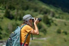 Ung fotograf som tar ett foto av landskapet arkivfoton