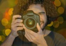 ung fotograf som tar ett foto (förgrund) med gräsplan- och gulingbokehbakgrund och överlappning arkivfoto