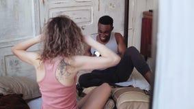 Ung fotografman som tar foto på flyttning-film kamera av den krullhåriga kvinnan i pyjamas Par i gladlynt lynne stock video
