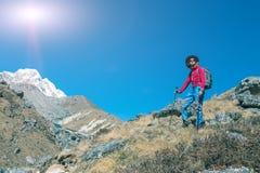 Ung fotvandrare som stiger ned på gräs- berglutning Arkivfoto