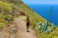 Ung fotvandrarekvinna som går på en slinga som förbiser havet i Tenerife royaltyfria bilder