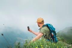 Ung fotvandrareman som tar bilden av molnig dalbotten genom att använda smartphonen under att gå vid det dimmiga molniga väderber royaltyfria bilder