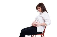 Ung framtida moder som förväntar en behandla som ett barn och poserar på stol Royaltyfria Foton