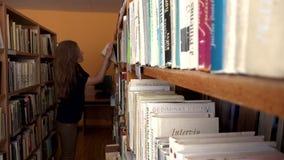 Ung föreläsarelärarekvinna som väljer böcker för föreläsning i universitetarkiv lager videofilmer
