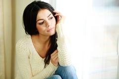 Ung fundersam kvinna som ser fönstret Fotografering för Bildbyråer