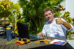 Ung funktionsduglig det fria för attraktiv och lycklig digital nomadman från coffee shop med bärbar datordatoren som ger tummen s Arkivfoton