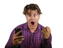 Ung galen lycklig och upphetsad man som firar framg?ng som g?r pengar som spelar direktanslutet med mobiltelefonen som segrar den arkivbild