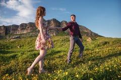 Ung gift par Grabben leder en lockig flicka med en bukett av blommor Royaltyfri Fotografi