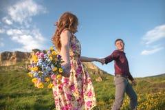 Ung gift par Grabben leder en lockig flicka med en bukett av blommor Royaltyfri Foto