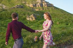 Ung gift par Grabben leder en lockig flicka med en bukett av blommor Arkivfoton