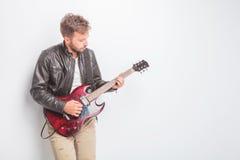 Ung gitarrist, i att spela för läderomslag royaltyfri foto