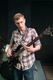 Ung gitarrist som spelar musik i studio royaltyfri fotografi