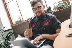 Ung gitarristhipster hemma med gitarren i sovrummet som dricker te genom att använda bärbara datorn arkivfoton