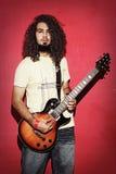 Ung gitarristman med härligt långt lockigt hår Arkivbild
