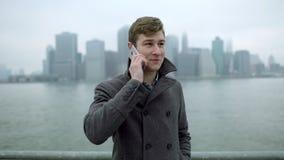 Ung glad man som tar påringning och talar över hans smartphone nära Hudson River med sikt på den Manhattan ön stock video