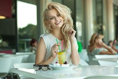 Ung gladlynt blondin i en drinkstång arkivbilder