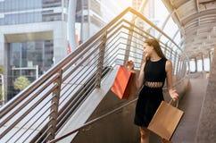 Ung gladlynt dam som smling och rymmer shoppingpåsar i gallerian, lycklig kvinnlig som ut går från varuhus royaltyfria bilder