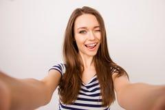 Ung gladlynt flicka i den randiga t-skjortan som tar selfie och att blinka arkivfoton