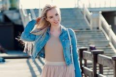Ung gladlynt flicka på kusten le kvinnabarn för blondin Moderiktig beige kjol fotografering för bildbyråer