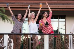 Ung gladlynt flickagrupp på balkong lyftta händer, härlig lycklig le kvinnavänkommunikation arkivfoton