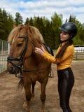 Ung gladlynt flickaryttare som kramar hennes favorit- röda häst Lodlinjen avbildar royaltyfria foton