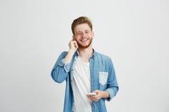 Ung gladlynt grabb i hörlurar som ler den hållande telefonen som ser kameran som lyssnar till musik över vit bakgrund royaltyfri foto