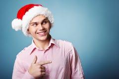 Ung gladlynt julman med punkt för hatt för santa ` s med handen le Royaltyfria Foton