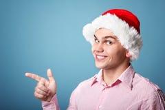 Ung gladlynt julman med punkt för hatt för santa ` s med handen le Arkivbild